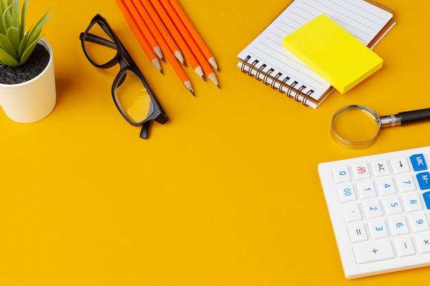 Elegante mesa bagunçada amarela com vários artigos de papelaria vista superior Foto Premium
