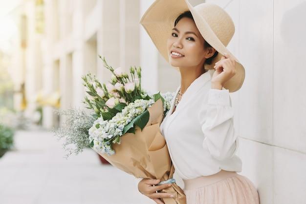 Elegante mulher asiática bem-vestida em grande chapéu de sol posando na rua urbana com flores Foto gratuita