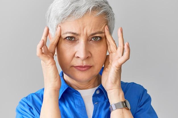 Elegante mulher branca de meia idade na camisa azul, sofrendo de enxaqueca. close de uma mulher madura estressada apertando as têmporas por causa de uma terrível dor de cabeça, massageando pontos doloridos Foto gratuita