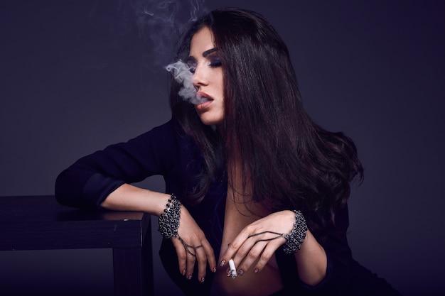 Elegante mulher morena gostosa fumando um cigarro Foto Premium