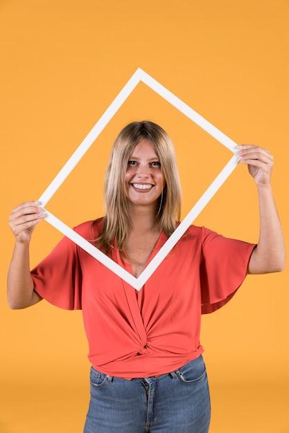 Elegante mulher segurando a moldura de foto de borda branca na frente de seu rosto Foto gratuita