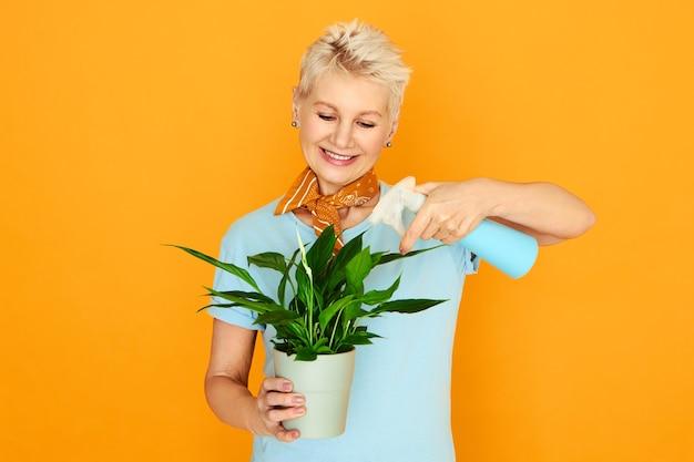 Elegante pensionista que passa o tempo dentro de casa cuidando da planta de casa. mulher aposentada segurando o pote, o borrifador, borrifando as folhas verdes da planta decorativa para remover a poeira e a sujeira. primavera e flor Foto gratuita