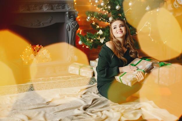Elegante, senhora jovem, sentando, perto, árvore natal Foto gratuita
