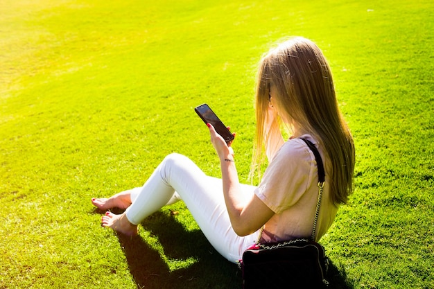 Elegante, senhora, verificações, dela, iphone, sentando, verde, gramado, parque Foto gratuita