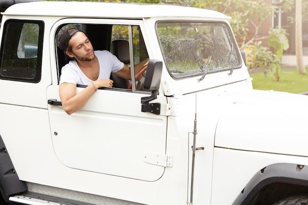 Elegante viajante caucasiano descansando durante a viagem de aventura de safari. homem jovem barbudo hipster em camiseta branca, sentado dentro de seu carro suv branco com tração nas quatro rodas e olhando pela janela aberta Foto gratuita