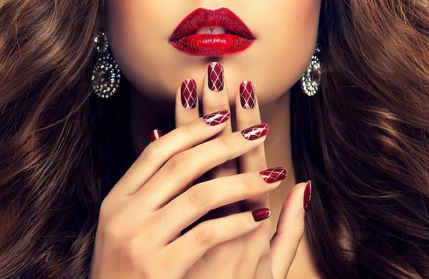 Elegantes mãos femininas com manicure profissionalmente feita nas unhas. dedos lindos, delgados e graciosos na frente dos lábios bem formados pintados com batom cereja. manicure, joias e cosméticos. Foto Premium