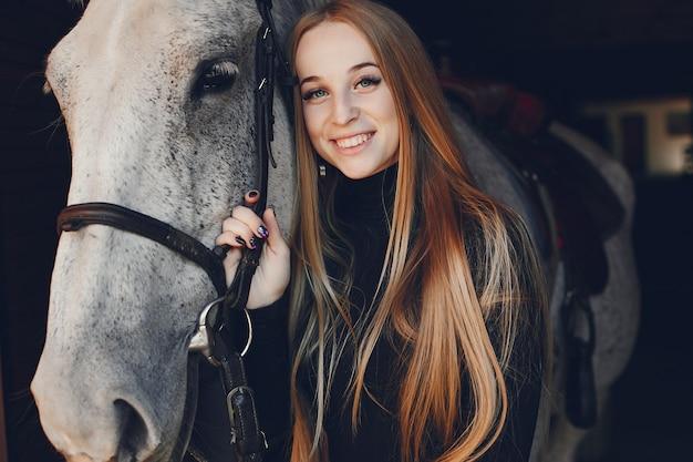 Elegants menina com um cavalo em uma fazenda Foto gratuita