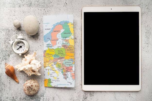 Elementos à beira-mar e tablet ajudando Foto gratuita