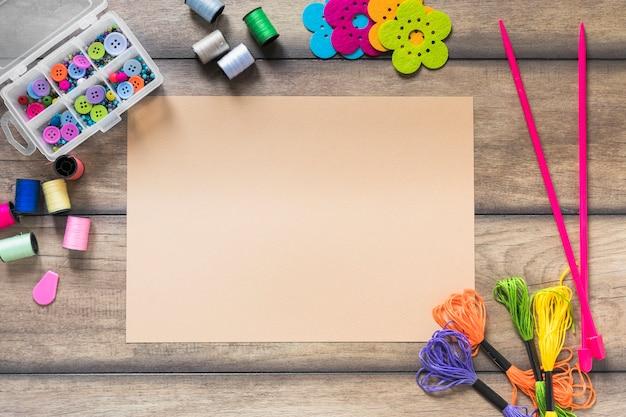Elementos decorativos cercados perto do papel em branco bege na mesa de madeira Foto gratuita