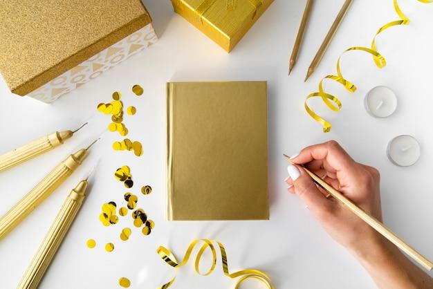 Elementos dourados com notebook e mão Foto gratuita
