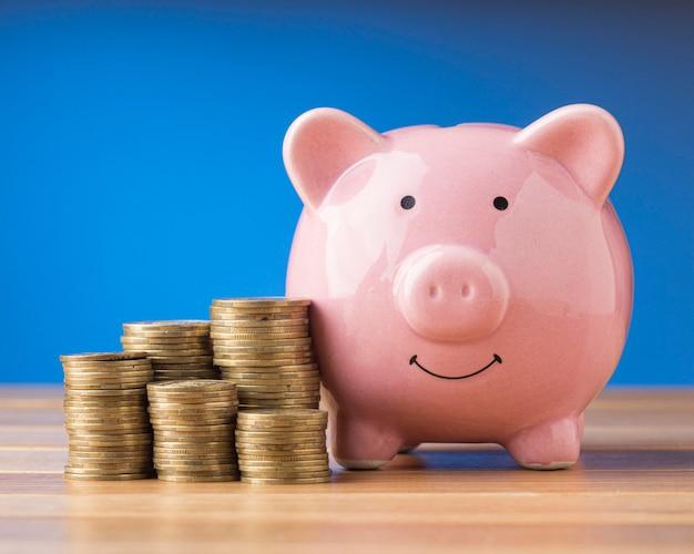 Elementos financeiros de vista frontal com cofrinho rosa Foto gratuita