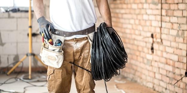 Eletricista com ferramentas, trabalhando em uma construção. conceito de reparo e faz-tudo. Foto gratuita