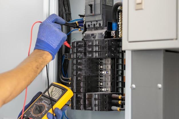 Eletricista está usando um medidor digital para medir a tensão no gabinete de controle do disjuntor Foto Premium