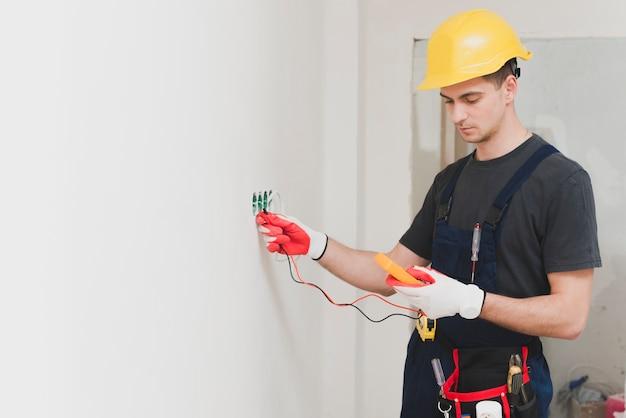 Eletricista fazendo medida no plugue Foto Premium