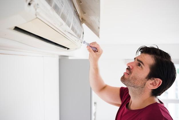 Eletricista masculina, verificando o condicionador de ar através do testador Foto Premium