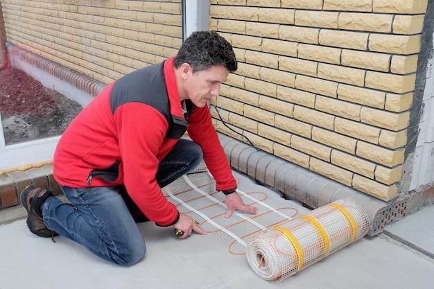 Eletricista que instala o cabo bonde de aquecimento no assoalho do cimento. Foto Premium