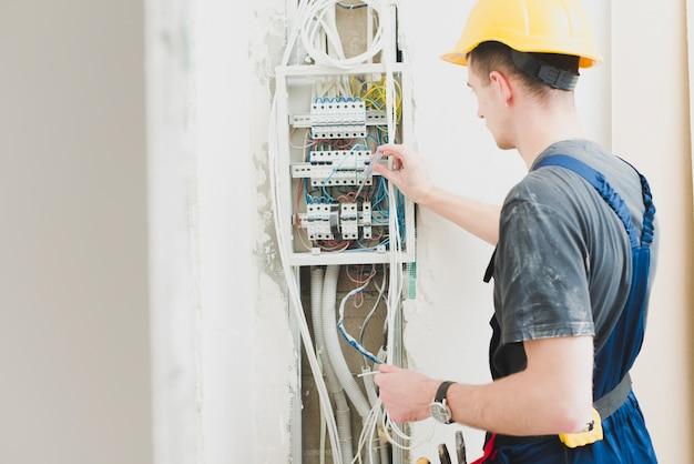 Eletricista que trabalha com painel de distribuição Foto gratuita