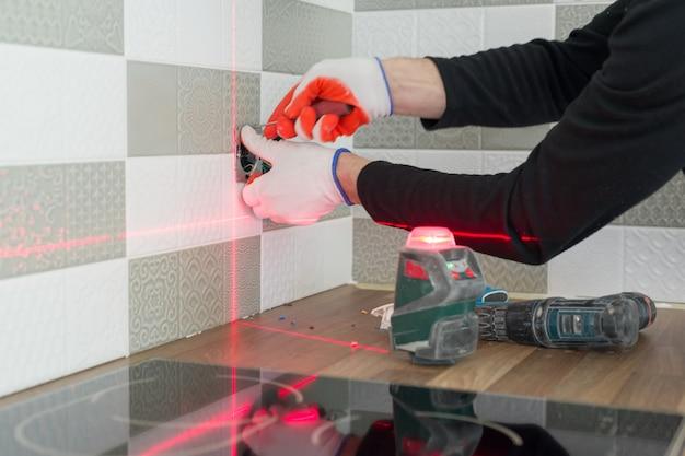 Eletricista usando nível de laser infravermelho para instalar tomadas elétricas. Foto Premium
