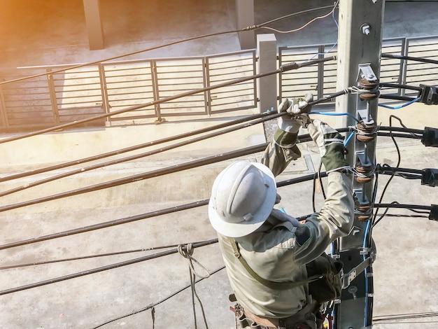 Eletricistas estão subindo em postes elétricos para instalar linhas de energia. Foto Premium