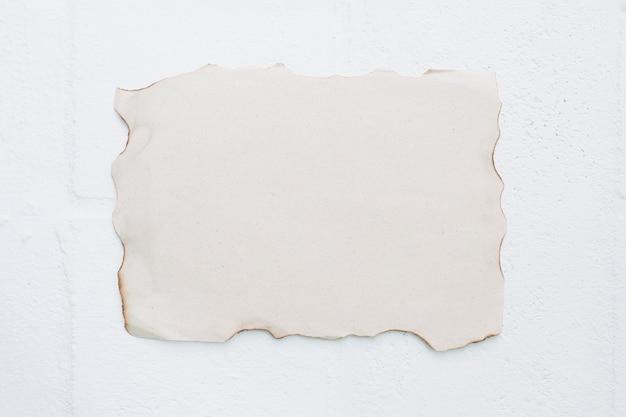 Em branco papel queimado contra fundo branco Foto gratuita