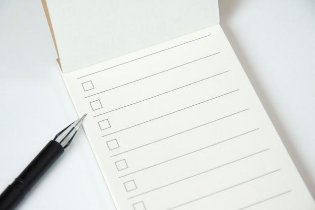 Em branco para fazer o planejador de lista com lista de verificação e caneta preta sobre fundo branco, close-up Foto gratuita