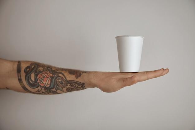 Em branco para tirar o vidro de papel na mão tatuada de homem brutal, apresentação de vista lateral isolada no fundo branco Foto gratuita
