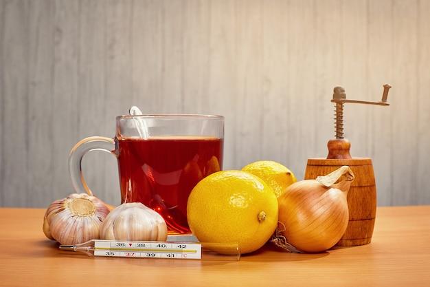 Em cima da mesa, uma caneca de chá com limão, cebola, alho e um termômetro Foto Premium