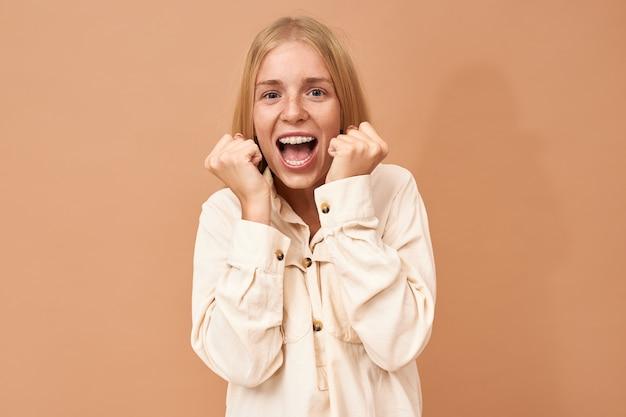 Em êxtase, jovem ganhador de sorte na loteria com aparelho dentário torcendo e comemorando o sucesso Foto gratuita