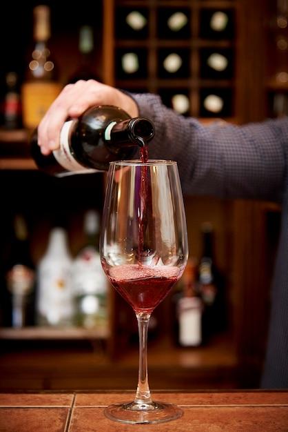 Em um copo com vinho tinto o barman derrama vinho de uma garrafa Foto Premium