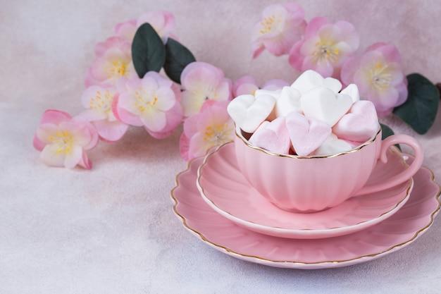 Em um copo rosa marshmallows em forma de coração e flores cor de rosa Foto Premium