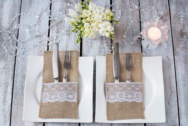 Em uma mesa de madeira branca, duas placas, velas, garfos e facas, flores em um vaso - um fundo festivo (aniversário, casamento, 8 de março, jantar romântico) Foto Premium
