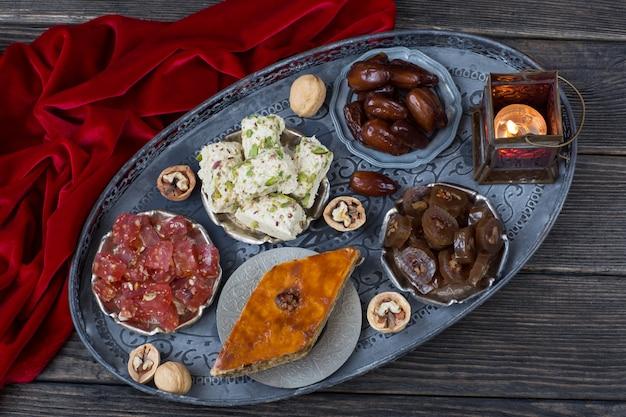 Em uma placa de prata datas, nozes, halva, delícia turca, baklava e uma lanterna Foto Premium