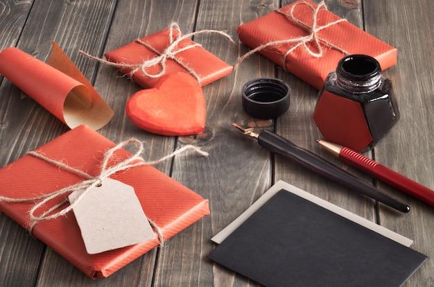 Embrulhado presentes, tinta e canetas para assinar cartões de presente na mesa de madeira Foto Premium