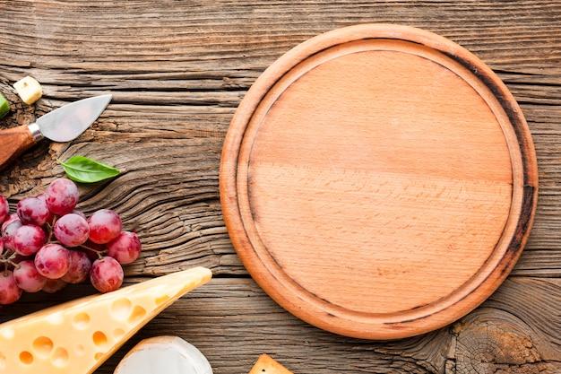 Emmental de uvas planas e faca de queijo com tábua de madeira Foto Premium