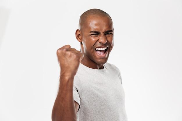 Emocional jovem africano em pé isolado fazer gesto vencedor Foto gratuita