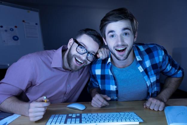 Emoções agradáveis. homem bonito e feliz, positivo, olhando para a tela do laptop e rindo ao ver algo engraçado Foto Premium
