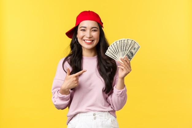 Emoções de pessoas, estilo de vida lazer e conceito de beleza. mulher 20s atraente feliz na tampa vermelha, apontando com orgulho em dinheiro. a mulher asiática satisfeita diz como ganhar o dinheiro em linha Foto Premium