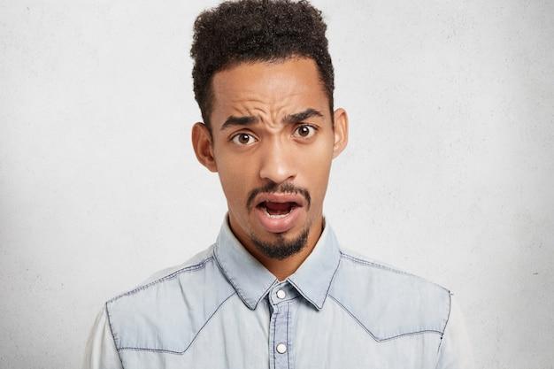 Emoções negativas e conceito de linguagem corporal. negro insatisfeito franze a testa e olha com a boca aberta Foto gratuita
