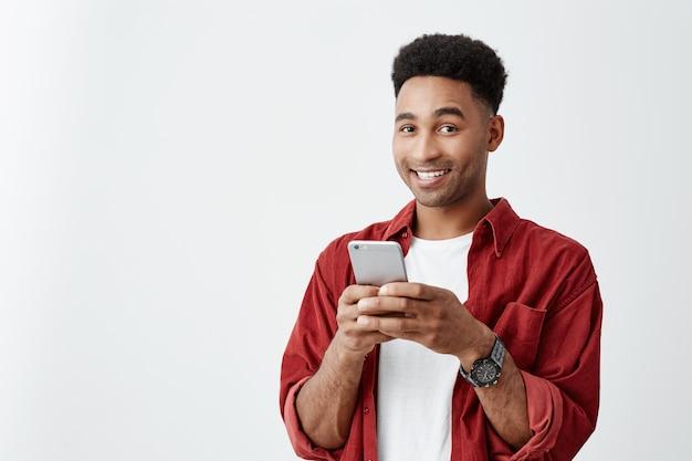 Emoções positivas. close-up de jovem bonito homem de pele escura com penteado afro em camiseta branca e camisa vermelha, sorrindo com dentes, conversando com um amigo no smartphone Foto gratuita