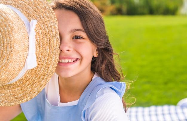 Emoticon menina cobrindo o olho com um chapéu de palha Foto gratuita