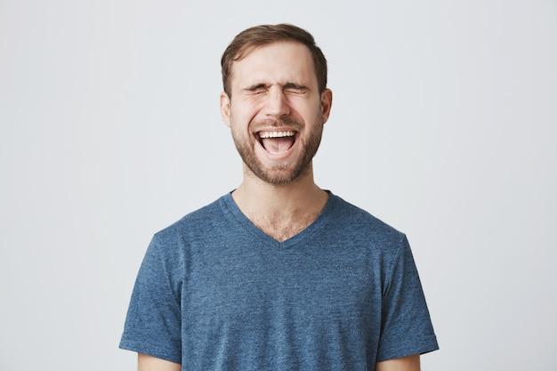 Emotivo barbudo fechar os olhos e gritando Foto gratuita