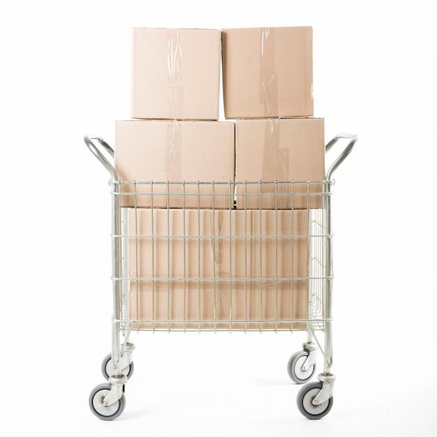 Empilhados de caixa de papelão no carrinho contra fundo branco Foto gratuita