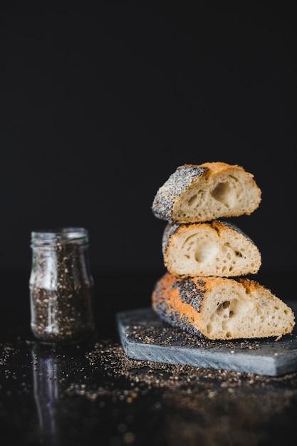 Empilhados de fatias de pão com sementes de chia na rocha contra o fundo preto Foto gratuita