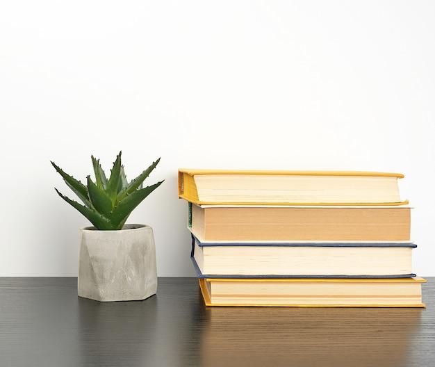 Empilhe livros sobre uma mesa preta e uma panela de cerâmica com uma planta verde Foto Premium