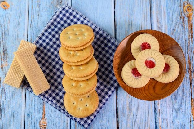 Empilhe muitos tipos de biscoitos em um prato e coloque sobre uma mesa de madeira. Foto gratuita
