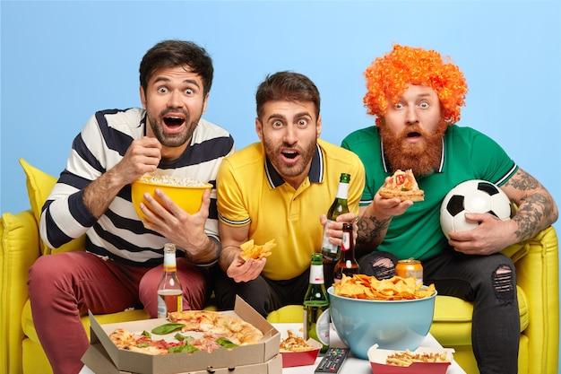 Empolgados três amigos do sexo masculino concentrados na tela do aparelho de tv, assistem a partida de futebol com grande interesse, posam no sofá da espaçosa sala de estar, comem pipoca Foto gratuita