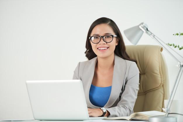 Empreendedor feminino, sorrindo com confiança para a câmera, sentado na mesa de trabalho Foto gratuita