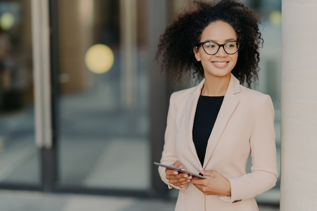 Empreendedor positivo mulher bem sucedida com cabelo afro detém tablet digital, fica ao ar livre perto de prédio de escritórios Foto Premium
