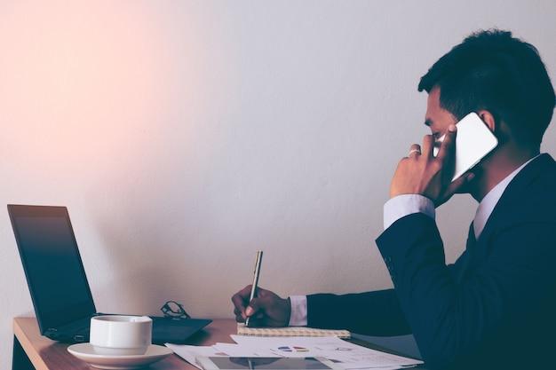 empreendedor trabalhando no telefone e escrevendo notas sentadas em uma mesa no escritorio 2379 644 - Seguro de Responsabilidade Civil: evitando prejuízos para o seu negócio