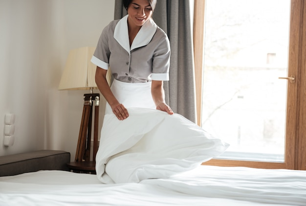 Empregada configurar lençol branco no quarto de hotel Foto gratuita